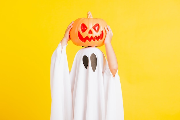 Little cute child with white dressed costume halloween ghost scary he holding orange pumpkin ghost on hand