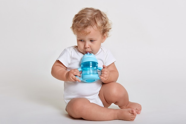 Little cute concentrated kid looking away while drinking water from baby cup, child with blonde curly hair sitting on floor