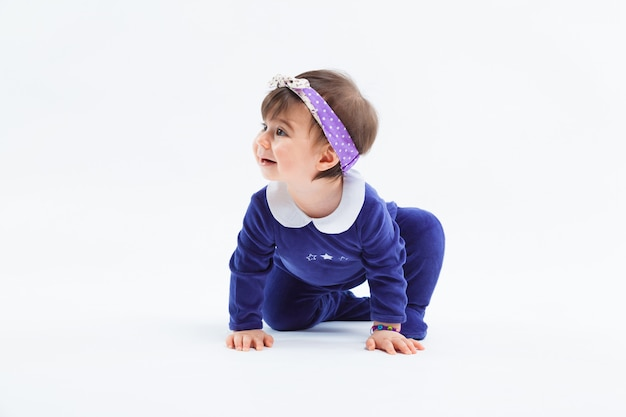 Little cute curious adorable smiling girl with bow in hair crawling sitting