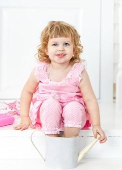 Маленькая милая кудрявая девушка в розовом платье в горошек улыбается, сидя на белой веранде в стиле прованс