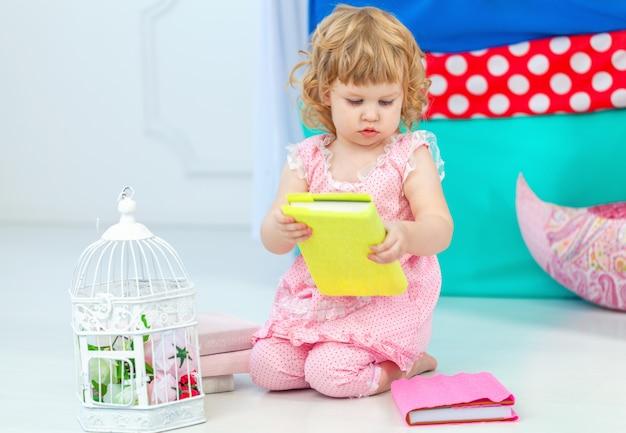 Маленькая милая кудрявая девушка в розовых пижамах, наблюдая за книгу, сидя на полу в детской спальне.
