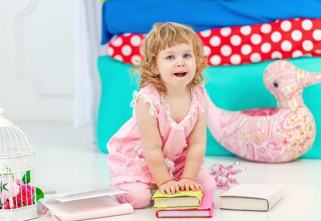 Маленькая милая кудрявая девушка в розовой пижаме, наблюдая за книгу, сидя на полу в детской спальне.