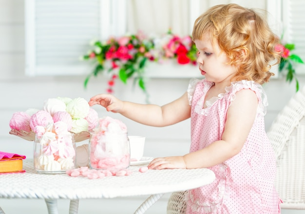 Little cute curly girl in a pink dress with lace and polka dots