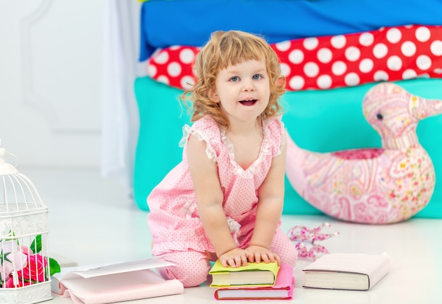 Little cute curly girl in pink pajamas watching the book sitting on the floor in the children's bedroom.