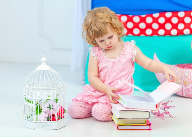 Little cute curly girl in pink pajamas watching the book sitting on the floor in children's bedroom.