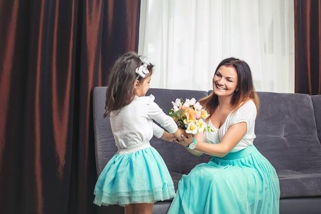 작은 귀여운 딸이 집에서 어머니의 날에 엄마에게 꽃을 줍니다