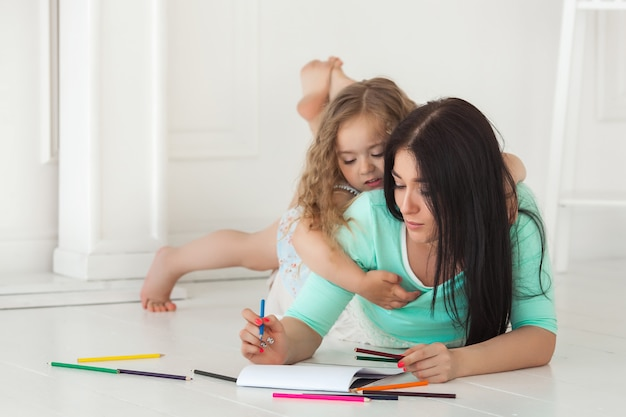 Little cute daughter and her mother drawing with colorful pencils and having fun together. pretty child and mom playing indoors. happy family spending time by drawing.