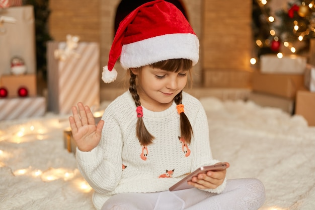 Little cute female kid with pigtails congratulation from home, smiling little girl using smart phone for video call, talks to somebody