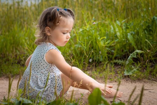 가벼운 드레스를 입은 귀여운 소녀 1-3은 여름에 잔디 배경의 들판에 있는 길에 앉아 있습니다.