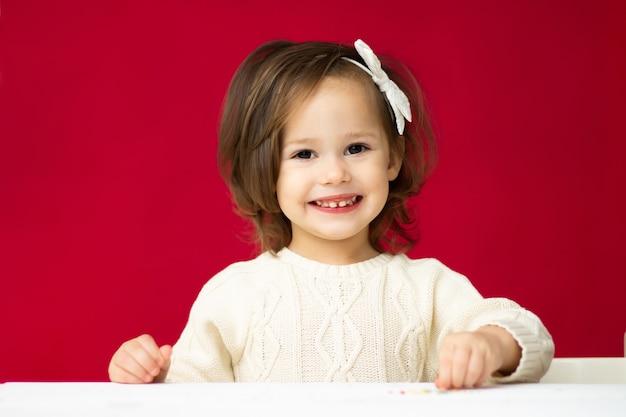 Маленькая милая девочка 2-4 в вязаном платье с белым бантом, улыбается на красном фоне.