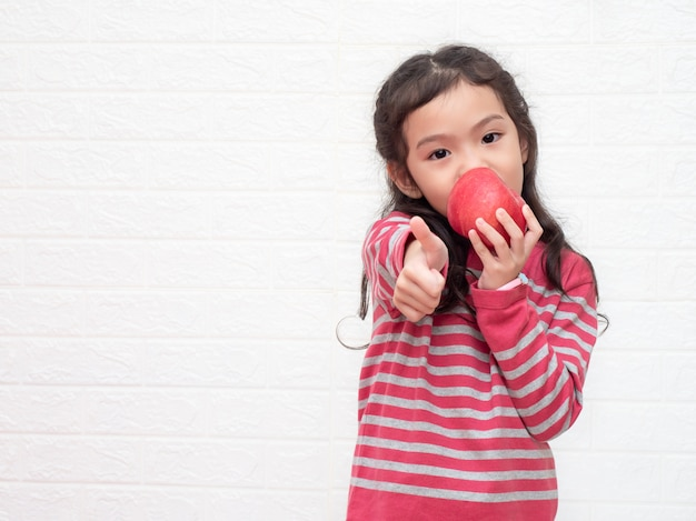 Little cute girl 6 years old eating red apple and trumps up on white bricks wall.