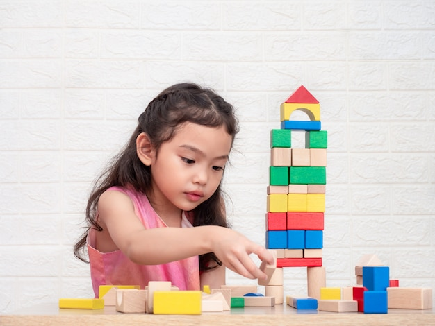 Little cute girl 6 years old playing wooden blocks on table and white bricks wall