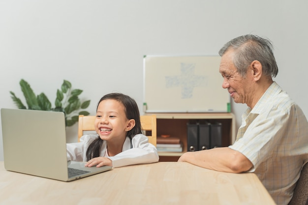 かわいい女の子とアジアのシニア男性が医師と患者の幸せな家族の時間を再生
