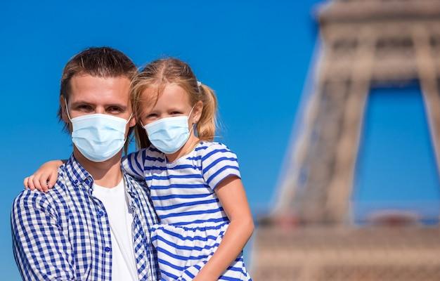 Маленькая милая девочка и ее отец в париже рядом с эйфелевой башней во время летних французских каникул