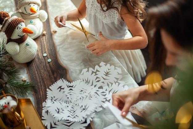 かわいい女の子と若い美しい女性は白い紙から雪片を切り取りました。ジンジャーブレッドとマシュマロ入りココア。新年とクリスマスの準備の概念。