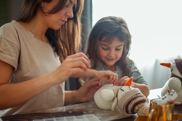 Маленькая милая девочка и молодая красивая женщина лепят вязанных снеговиков, мама и дочка пришивают пуговицы