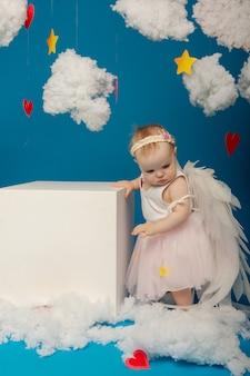 バレンタインデーの青い背景の上の小さなかわいい女の子の天使