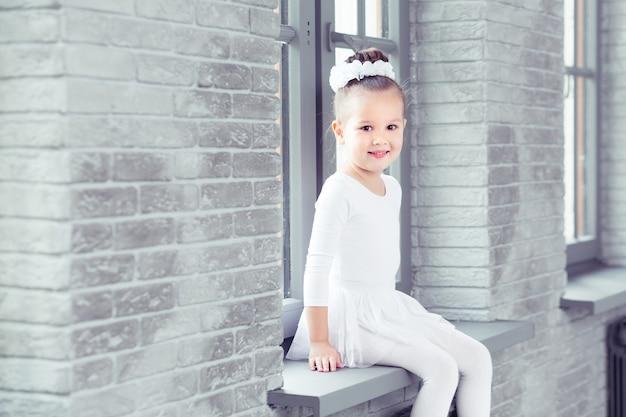 Маленькая милая девушка-балерина на фоне класса современного танца, глядя в камеру