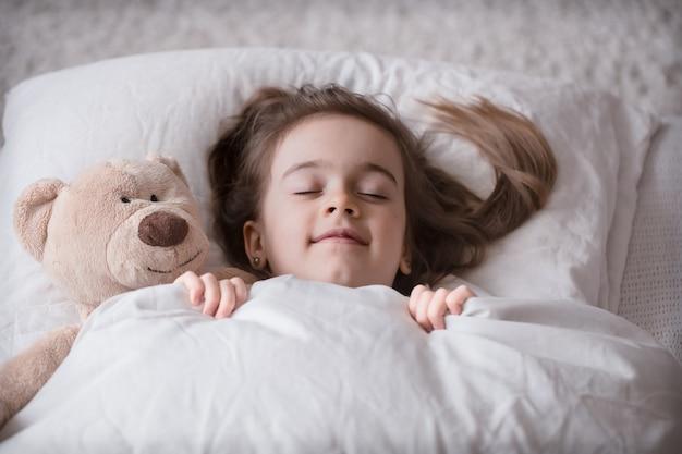 Piccola ragazza carina a letto con il giocattolo