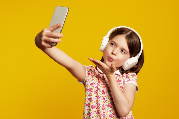 Маленькая милая девочка отправляет воздушный поцелуй в камеру смартфона и делает селфи