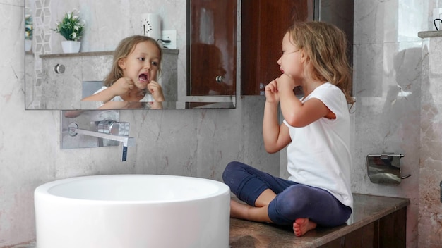 Little cute girl brushes her teeth with dental floss in front of the mirror