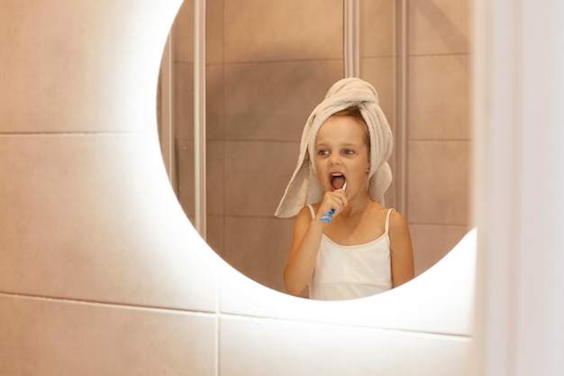 Little cute girl brushing teeth in bathroom, looking at her reflection in the mirror, wearing white sleeveless t shirt, wrapped hair in towel, hygienic procedures in the morning or before going to bed