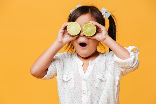 Little cute girl child covering eyes with lime.