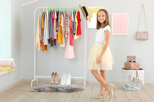 Маленькая милая девочка выбирает одежду в гардеробной