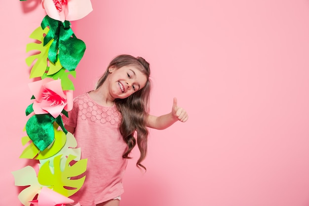 Little cute girl on color background with paper flowers , place for text, summer advertising concept
