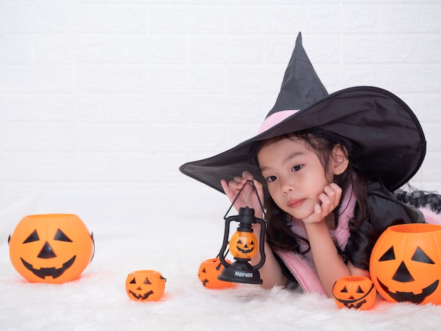 Little cute girl cosplay as a witch and holding the pumpkins lamp and buckets on white background.