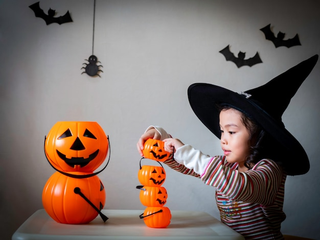 Little cute girl cosplay as a witch and play stack the pumpkins buckets over dark background with spiders and bats.