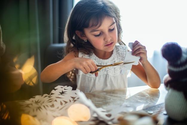 Маленькая милая девочка вырезает снежинки из белых бумажных имбирных пряников и какао с зефиром ...