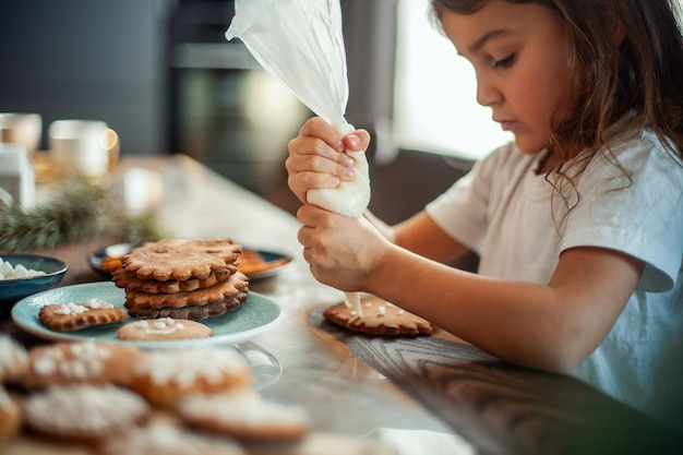 Little cute girl decorates gingerbread with sugar icing. preparation for christmas concept.