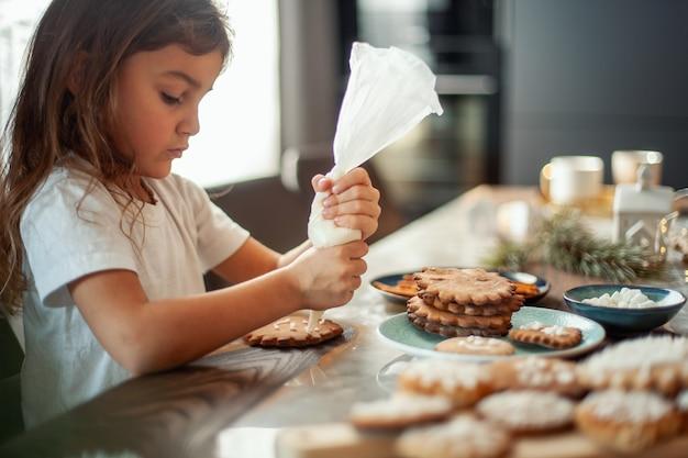 かわいい女の子がジンジャーブレッドを砂糖のアイシングで飾ります。クリスマスのコンセプトの準備。