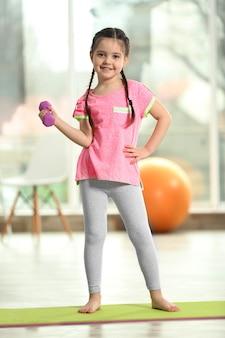 Маленькая милая девочка делает упражнения с гантелями на коврике в помещении