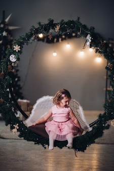 A little cute girl in a dress with angel cruces sits in a large round scenery of spruce branches