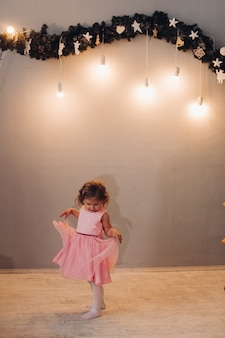 A little cute girl in a dress with curly hair looks at her dress near the garland