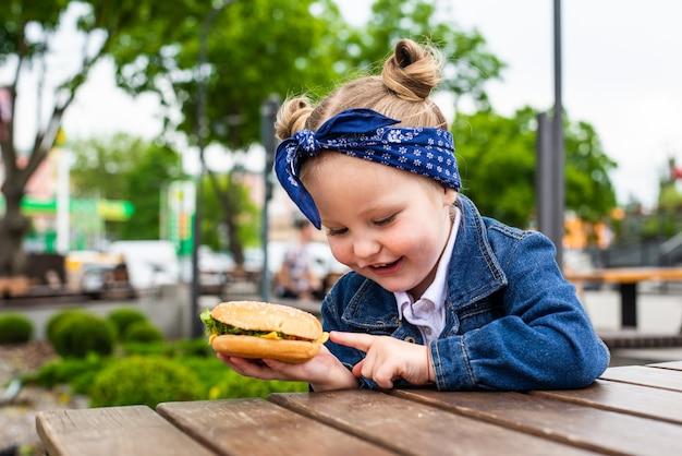 Маленькая милая девочка ест гамбургер в кафе. концепция детского фаст-фуда