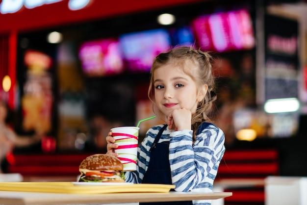 Маленькая милая девочка ест гамбургер в кафе, концепция детского фаст-фуда