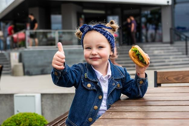 Маленькая милая девочка ест гамбургер показывает палец вверх в кафе. концепция детского фаст-фуда