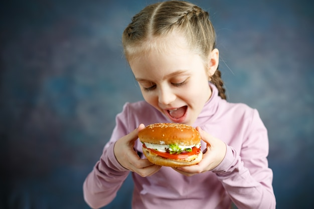 Little cute girl eating a burger in a cafe, concept of a children's fast food meal