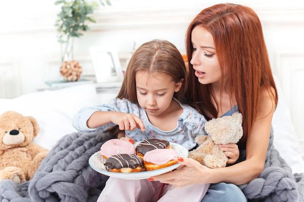 Bambina carina godendo, giocando e creando con la torta con la madre
