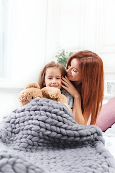 A little cute girl enjoying, playing and creating with toy with mother