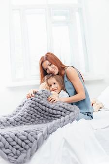 Bambina carina godendo, giocando e creando con il giocattolo con la madre