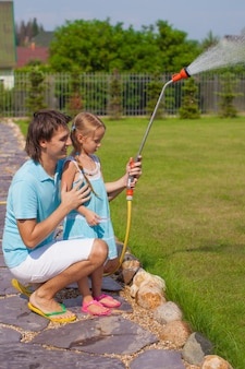 Little cute girl and father watering flowers with hose in their garden