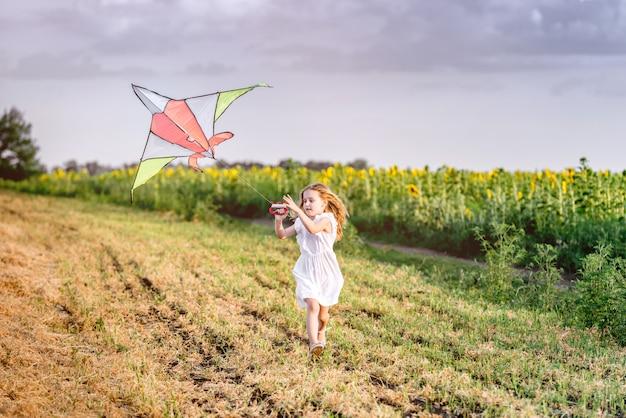 Little cute girl flying a kite