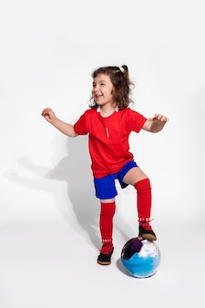 Little cute girl in football uniform and with ball