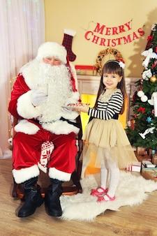 Маленькая милая девочка дает печенье и молоко деду морозу возле елки дома