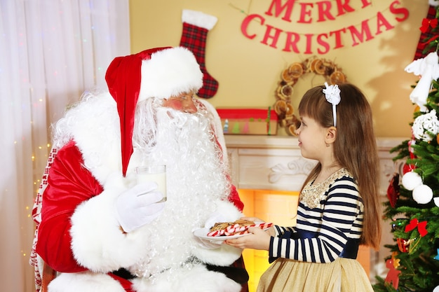 Little cute girl giving cookies and milk to santa claus near christmas tree at home