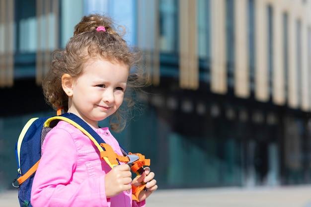 Маленькая милая девочка идет в первый класс. счастливый ребенок вернулся в школу. ребенок с рюкзаком, школьный портфель на синем фоне на capmus снаружи.